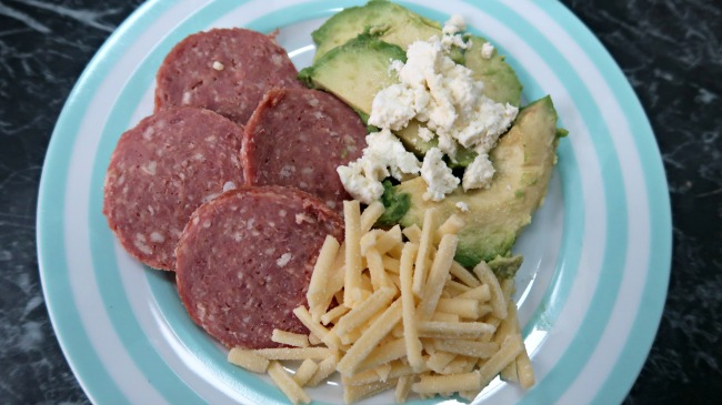 Keto breakfast without eggs platter of salami, avocado, feta and grated cheese