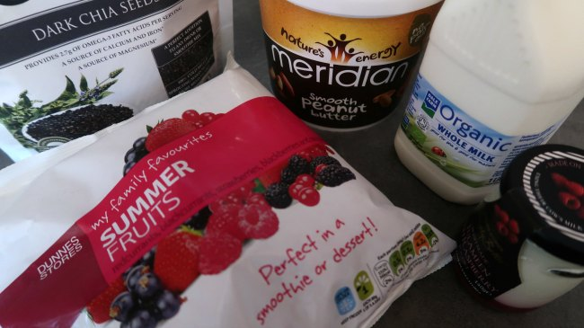 Ingredients for healhty protein smoothie with peanut butter and berries